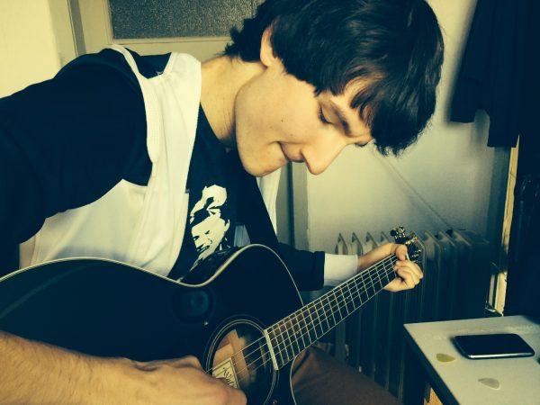 Florian Eib blickt konzentriert auf eine Gitarre in seiner Hand. Mit einer Hand zupft er die Saiten. Er trägt ein T-Shirt, auf dem der Kopf eines anderen Sängers abgebildet ist, Foto: Friedrich Ziller