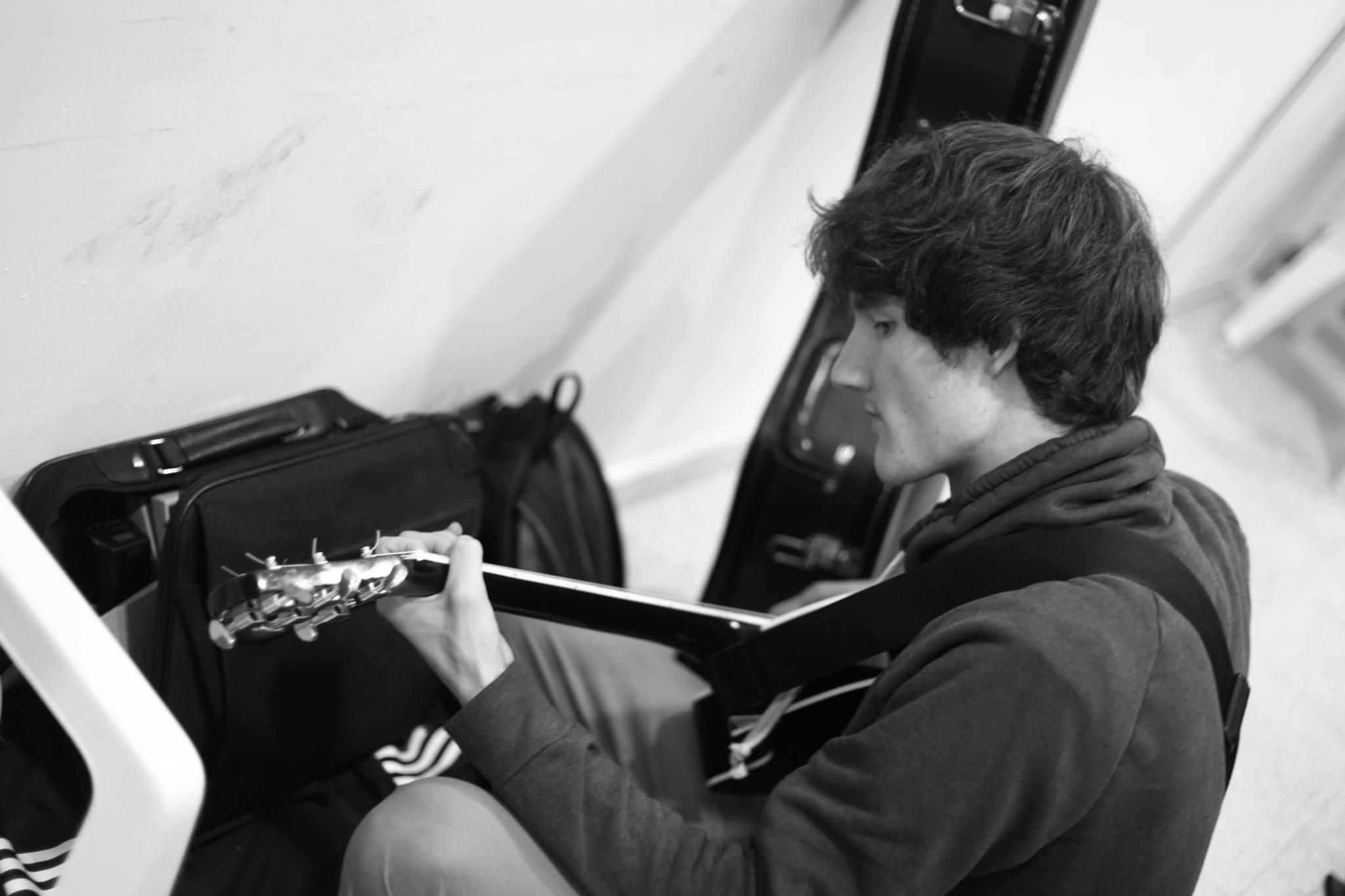 Ein Schwarz-weiß-Foto zeigt den Musiker und Sänger Florian Eib von schräg oben mit einer Gitarre in der Hand. Florian blickt konzentriert auf das Griffbrett der Gitarre. Im Hintergrund stehen eine Reisetasche und ein Gitarrenkoffer, Foto: Hagen Ebrecht.