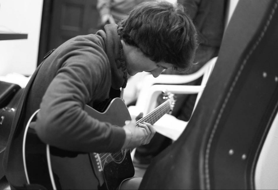 Ein Schwarz-Weiß-Foto zeigt den Sänger und Musiker Florian Eib aus der Seitenperspektive. Florian ist über seine Gitarren in den Händen gebeugt und schlägt mit einer Hand an. Er trägt dunkle halblange Haare. Am rechten Bildrand befindet sich der obere Teil eines Gitarrenkoffers, Foto: Hagen Ebrecht.