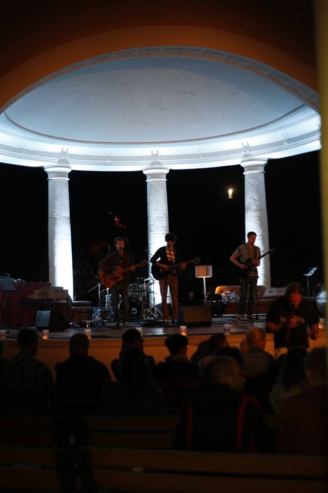 Das zeigt Zuschauerinnen und Zuschauer auf dem KleinKlang-Festival 2014 in Eisenach von hinten. Im Hintergrund stehen die Musiker der Band Strandheizung auf einer leicht erhöhten runden Bühne der Eisenacher Wandelhalle. Sie stehen im schwachen Licht. Hell beleuchtet sind die weißen hoch aufragenden Säulen im Hintergrund. Foto: Hagen Ebrecht.