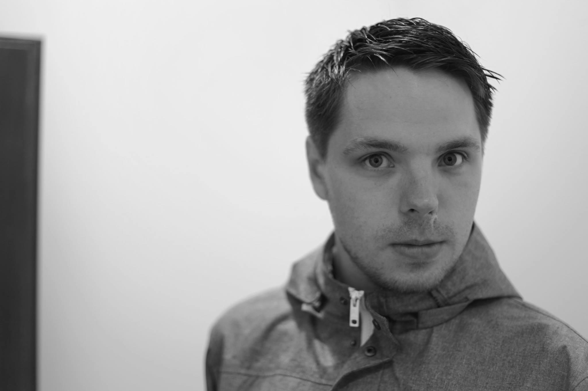 Ein Schwarz-Weiß-Portrait zeigt Marcus Gloge, den früheren Gitarristen der Band Strandheizung. Sein Gesichtsausdruck ist neutral. Er trägt kurze dunkle gegeelte Haare, Foto: Hagen Ebrecht.
