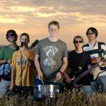 Die Band Strandheizung steht in einem Roggenfeld. Die Musiker haben ihre Instrumente dabei und stehen gerade nebeneinander den Blick zur Kamera gewandt, Foto: Jim Cramer.