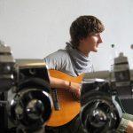 Florian Eib mit langen braunen Haaren sitzt mit der Gitarre in der Hand vor einer weißen Wand und blickt zur Seite, Foto: Hagen Ebrecht.