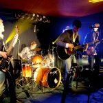 Die Band Strandheizung auf einer kleinen Bühne mit Schlagzeug, E-Gitarren und Mikrofonen während eines Liedes, Foto: Strandheizung.