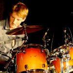 Schlagzeuger Volker Westhaus bei einem Auftritt mit der Band Strandheizung. Er blickt konzentriert während er spielt, Foto: Strandheizung.