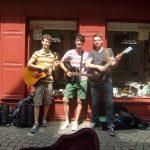 Die Musiker Florian Eib, Dominic Eib und Marcus Gloge stehen vor einem Schaufenster auf einer bepflasterten Straße. Sie haben ihre Instrumente – Gitarren – umgehängt und blicken lächelnd in Richtung Kamera, Foto: Strandheizung.