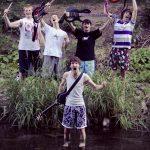 Die Musiker der Band Strandheizung am Rand eines Flussufers mit ihren Instrumente. Gitarrist und Songwriter Florian Eib steht bis zu den Knien im Wasser. Alle zusammen machen Jubelposen, Foto: Paul Ruben Mundthal.