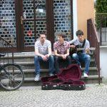 Die Musiker der Band Strandheizung sitzen auf einer Steintreppe mit Geländern, die zu einer Glasflügeltür hinauf führt. Florian Eib spielt Gitarre, vor ihnen steht ein offener Gitarrenkoffer, Foto: Michelle Eib.