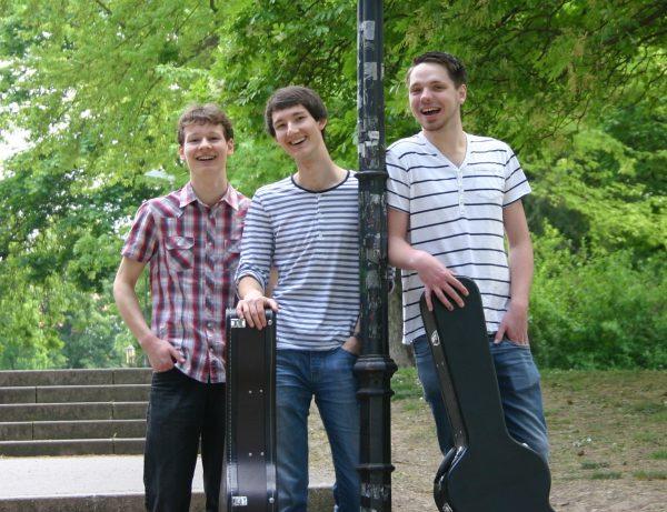 Drei Musiker der Band Strandheizung Dominic Eib, Florian Eib und Marcus Gloge stehen um eine alte Laterne herum und blicken lächeln in die Kamera. Im Hintergrund wachsen zahlreiche Bäume und grüne Pflanzen, Foto: Michelle Eib.