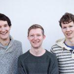 Die Musiker Florian Eib, Dominic Eib und Johannes Rebel in einem Portraitfoto. Sie stehen vor einer weißen Wand und blicken lächelnd in die Kamera, Foto: R. Kube.