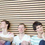Die Musiker Florian Eib, Dominic Eib und Johannes Rebel in einem Portraitfoto. Sie sitzen vor einer hölzernen Wand und blicken abwechselnd lächelnd und nachdenklich in die Kamera, Foto: R. Kube.