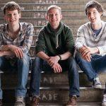 Die drei Musiker Dominic Eib, Johannes Rebel und Florian Eib von links nach rechts. Auf diesem Portraitfoto sitzen sie auf einer Steintreppe und lächeln in die Kamera, Foto: R. Kube.