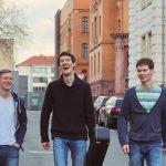 Zu sehen ist die Singer-Songwriter-Band Strandheizung im Jahr 2017. Fotografiert von Thomas Witte. Die drei Musiker laufen eine Straße zwischen Backsteinhäusern entlang. Florian trägt einen Gitarrenkoffer in der Hand.