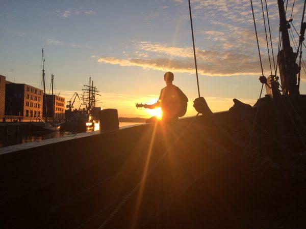 Der Moment eingefangen in einem romantischen Bild, das Florian Eib mit Gitarre auf der Reling eines Schiffes am Wismarer Hafen. Florian ist von der untergehenden Sonne beschienen, Foto: Dominic Eib.