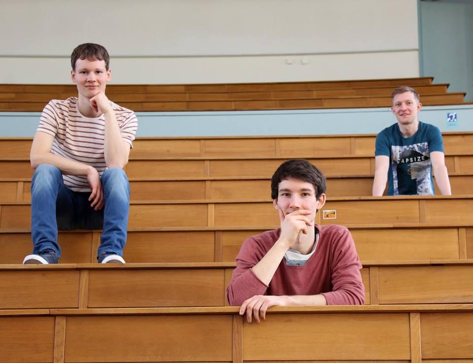 Die Musiker der Band Strandheizung Florian, Dominic und Johannes sitzen verteilt in einem großen Hörsaal mit Holztischen und Bänken. Das Foto wurde aus der Froschperspektive geschossen, Foto: Thomas Witte.