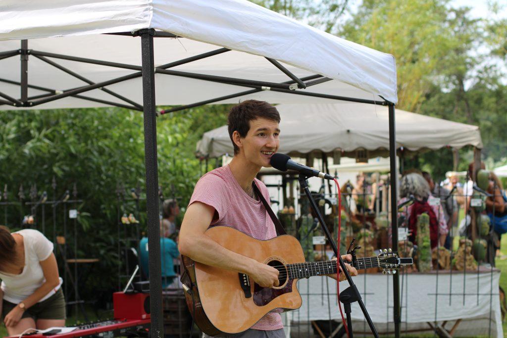 Auftrittsfoto der Singer-Songwriter-Band Strandheizung beim Töpfermarkt Ratzeburg im Juli 2019. Zu sehen ist Florian Eib an der Akustikgitarre. Foto: Uwe Koop