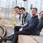 Strandheizung sitzt an einem Bahnsteig. Im Hintergrund sind Schienen und eine Ampelanlage zu erkennen. Die vier Bandmitglieder lachen in die Kamera, Fotografiert von Thomas Witte im März 2019. Kontakt: mail@strandheizung.com