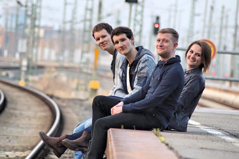 Strandheizung sitzt an einem Bahnsteig. Im Hintergrund sind Schienen und eine Ampelanlage zu erkennen. Die vier Bandmitglieder lachen in die Kamera, Foto: Thomas Witte. Kontakt: mail@strandheizung.com