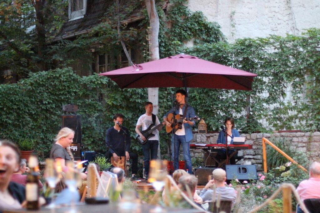 Auftrittsbild der Singer-Songwriter-Band Strandheizung 2020: Die Band am Rande des Künstlergartens. Die vierköpfige Band steht unter einem roten Schirm. Vor der etwas erhöhten Bühne sind zahlreiche sitzende Zuschauer, Foto: Volker Westhaus.