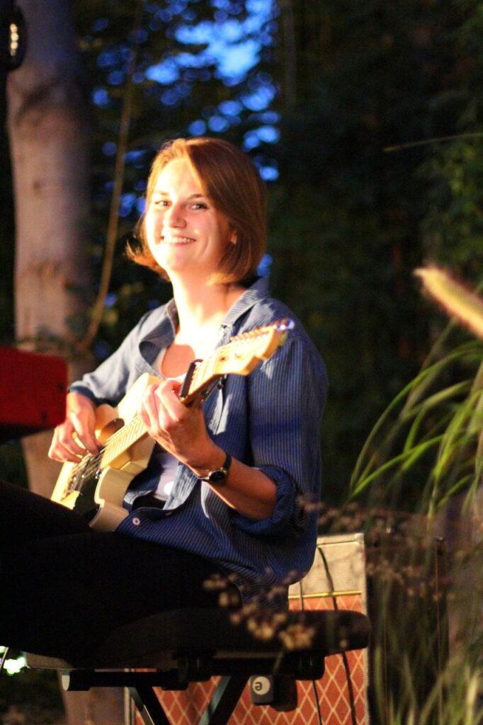 Auftrittsbild der Singer-Songwriter-Band Strandheizung beim Kunstfest Weimar 2020: Tomke Koop an der E-Gitarre sitzt auf einem Klavierhocker und blickt lächelnd in die Kamera, Foto: Volker Westhaus.