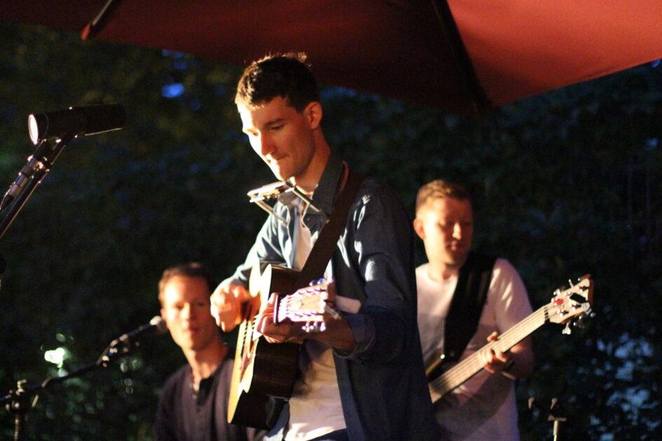 Die Singer-Songwriter-Band Strandheizung bei einem Auftritt beim Kunstfest in Weimar 2020: Florian Eib an der Gitarre und mit einer Mundharmonika um den Hals. Im Hintergrund sind Dominic Eib und Johannes Rebel an ihren Instrumente, Foto: Volker Westhaus.