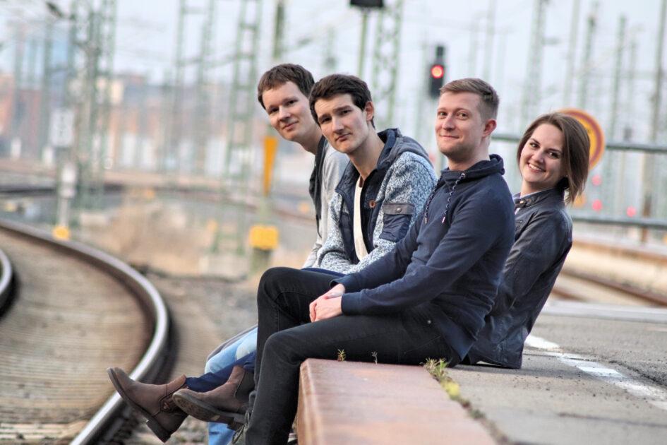 Pressebild der Singer-Songwriter-Band Strandheizung aus dem Jahr 2019. Die vier Musiker sitzen an einem verlassenen Bahnsteig und lassen die Beine über dem Gleisbett baumeln, Foto: Thomas Witte.