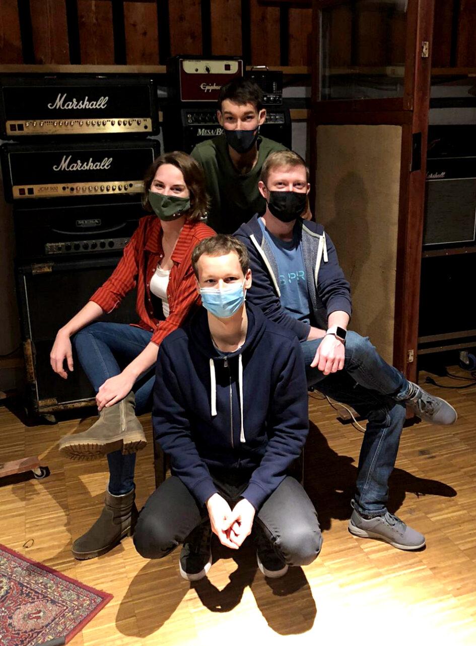 Recording Wunderkinder: Strandheizung, bestehend aus Florian, Dominic, Johannes und Tomke sitzen vor großen Gitarrenverstärkern und lächeln in die Kamera. Die vier haben verschiedenfarbige Masken auf, Foto: Frithjof Rödel.